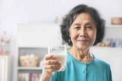 den glass holdingen mjölkar den höga kvinnan Royaltyfri Bild