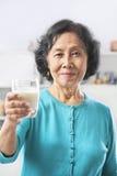 den glass holdingen mjölkar den höga kvinnan Royaltyfri Foto