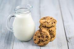 Den Glass tillbringaren med mjölkar och choklade kakor på träbakgrund Royaltyfri Fotografi