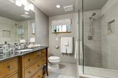 Den gråa badruminre med exponeringsglas går i dusch royaltyfri foto
