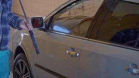 Den gråa bilen tvättas med högtrycks- vatten på en biltvätt arkivfilmer