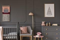 Den gråa fåtöljen med rosa färger kudde mellan säng och kabinettet i barn`, arkivfoto