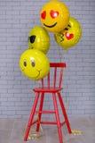 Den gråa lägenhetstudion med stol, tegelstenväggen, guling specificerar röd stol för ballongemojien royaltyfri foto