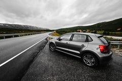 Den gråa moderna bilen parkerar bredvid en lantlig stenlagd väg som leder till och med naturen av Norge så långt, som ögat kan se arkivfoto