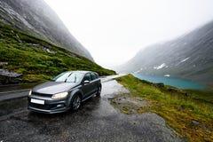 Den gråa moderna bilen parkerar bredvid en lantlig väg i en dal som in omges av en fjord och snö täckte berg på en regnig dag ell royaltyfri fotografi