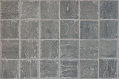 Den gråa stenen belägger med tegel bakgrund Arkivfoton