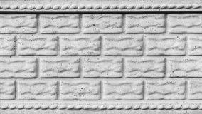 Den gråa texturen av en betongvägg med sprickor, efterföljd av stenkvarter eller tegelstenar, abstrakt bakgrund för arkitektur royaltyfri foto
