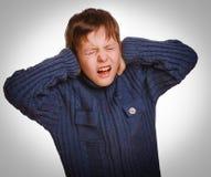 Den gråa tonårs- pojken stängde hans öron öppnade ropa för mun Arkivbild