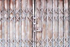 Den gråa vikningståldörren i flätar samman modeller för bakgrund och tre rostiga gamla låsta royaltyfria foton