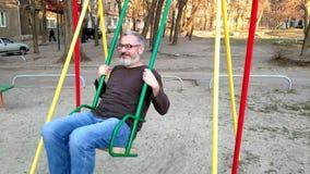 Den gr?h?riga sk?ggiga mannen som rider p? en gunga, jublar och ler, begreppet av en lycklig barndom stock video
