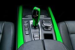 Den gröna automatiska växelspaköverföringen av en modern bil-, multimedia- och navigeringkontroll knäppas Bilinredetaljer Sändare arkivfoton