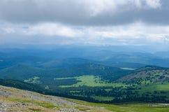 Den gröna dalen som är hög på bergen med sikten som gör klar himmel i sommardag, spangleds med att blomma blommor Arkivfoton