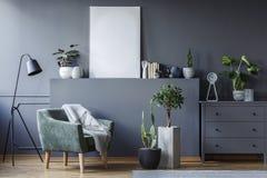 Den gröna fåtöljen mellan den svarta lampan och växter i grå färger sänker interi royaltyfria foton