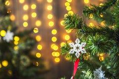 Den gröna julgranen dekorerade med julleksaker och en girland med gula ljus Arkivfoton