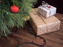 Den gröna julgranen som dekorerades med leksaker och girlanden, ledde ljus Boxas gåvor Royaltyfri Bild