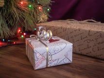 Den gröna julgranen som dekorerades med leksaker och girlanden, ledde ljus Boxas gåvor Royaltyfri Fotografi