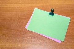Den gröna klistermärken med en paperclip som isoleras på träbakgrund Royaltyfria Foton