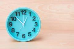Den gröna klockan på wood bakgrund, klockan som berättar tid, skapar plommoner Arkivfoton