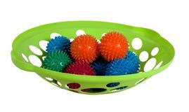 Den gröna koppen med behandla som ett barn massagebollar Arkivbild