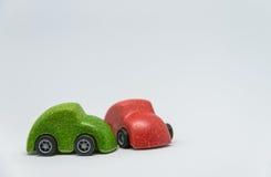 Den gröna leksakbilolyckan kraschade den röda leksakbilen med vit bakgrund och den selektiva fokusen Royaltyfri Foto