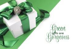 Den gröna och vita gåvan med härliga satängband- och gräsplangåvor är det ursnygga prövkopiahälsningmeddelandet Fotografering för Bildbyråer