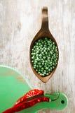 Gröna peppercorns i bunke och röda chilir på grönt trä stiger ombord Royaltyfri Fotografi