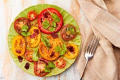 Den gröna plattan av sallad med skivade tomater tjänade som på trätabellen Royaltyfri Fotografi