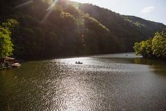 Den gröna sjön av Hamori i Lillafure nära Miskolc, Ungern Vårlandskap med solstrålar som täcker bergen Den sol- banan arkivfoto