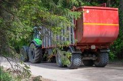 Den gröna traktoren bär en röd släp arkivfoto