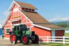 Den gröna traktoren och den röda ladugården med blå himmel och vit fäktar Arkivfoton