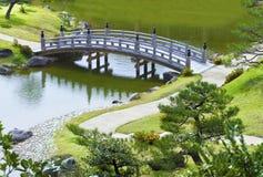 Den gråa lilla bron och curvy går vägen i en trädgård Arkivbild