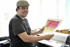 Den grafiska formgivaren kontrollerar färgen med färgprovkarta Arkivfoton
