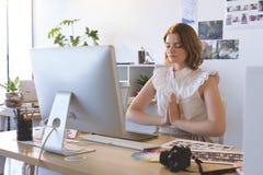 Den grafiska formgivaren med handen kn?ppte fast att g?ra yoga i id?rikt kontor royaltyfri bild