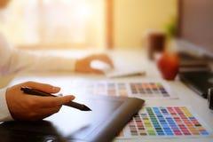 Den grafiska formgivaren räcker genom att använda den digitala minnestavlan och datoren royaltyfri fotografi