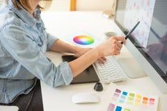 Den grafiska rengöringsdukformgivaren gör arbetet genom att använda en diagramminnestavla, skrivbord arkivbilder