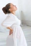Den gravida asiatiska kvinnlign som har tillbaka, smärtar Fotografering för Bildbyråer