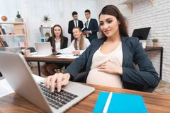 Den gravida attraktiva kvinnan skriver på bärbar datortangentbord Havandeskap i regeringsställning fotografering för bildbyråer