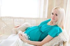 Den gravida blonda kvinnan som kopplar av på sofaen, läsning bokar och att drömma, Arkivbild