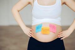 Den gravida bukpojkeflickan kopplar samman bilder på klistermärkear, kvinnan som förväntar, behandla som ett barn, familjbarnuppf Arkivbild