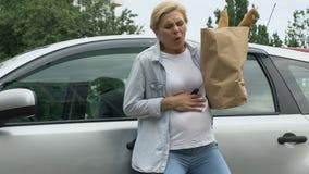 Den gravida damen har missfallet på grund av den tunga påsen med livsmedel, före födseln omsorg arkivfilmer
