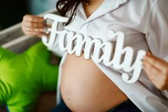 Den gravida flickan är hållande träbokstäver familj, sitter rymmer gravida kvinnan i en vit skjorta på sängen och bokstavsfamilje Royaltyfria Bilder