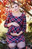 Den gravida flickan bär den rutiga klänningen parkerar in Royaltyfri Fotografi
