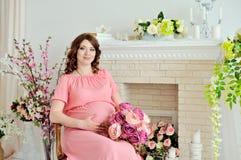 Den gravida flickan i rosa färger klär sammanträde på en stol i studion som rymmer blommorna i hans hand och ser kameran Fotografering för Bildbyråer
