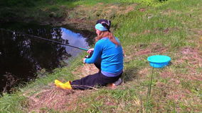 Den gravida flickan sitter på sjökust och fångar fisken med den gulliga katten lager videofilmer