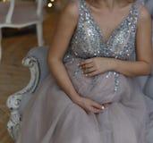Den gravida flickan sitter på soffan i en blå klänning med mousserar royaltyfri foto