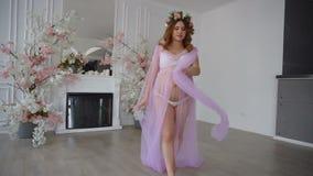 Den gravida härliga unga kvinnan i lila peignoir och blom- head krans går på lyxigt rum lager videofilmer