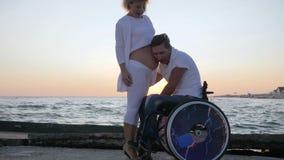 Den gravida kvinnlign med den ogiltiga maken i rullstol på solnedgången, den lyckliga handikappade personen smeker kvinnan med de lager videofilmer