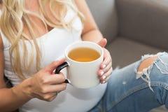 Den gravida långa kvinnan för blont hår rymmer en råna av te royaltyfri fotografi