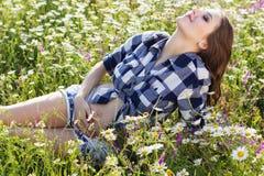 Den gravida le kvinnan på fält av tusenskönan blommar Arkivbild