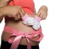 Den gravida mamman i underkläderna som spelar med, behandla som ett barn byten Buk med det rosa bandet långsam rörelse royaltyfri fotografi